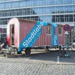 Während der Vorbereitungen: Das mobile Projektbüro im rot-weiß gestreiften Bauwagen stand vor der Eröffnung rund sechs Wochen am zentral gelegenen Osthafenplatz. Foto: hmf, K. Weber